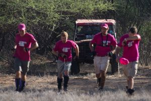 Bundu Fundi team 38 arrives at the checkpoint with runners in front. This team is the Avery family. The father lives in Nairobi, and the children, many doctors, come every year from England to compete in the Rhino Charge.